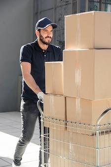 Lieferbote mit paketen gehend auf bürgersteig