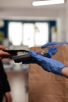 Lieferbote mit schutzhandschuhen, die zahlung erhalten