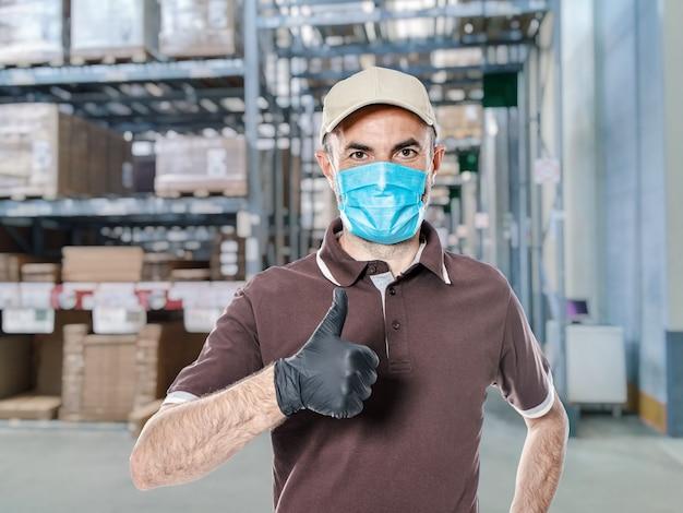 Lieferbote mit uniform und schutzmaske für covid-19 in einem lagerhaus. sicheres versandkonzept.