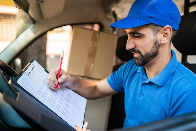 Lieferbote prüft lieferliste im lieferwagen