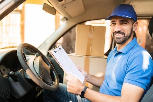 Lieferbote prüft lieferliste im lieferwagen.