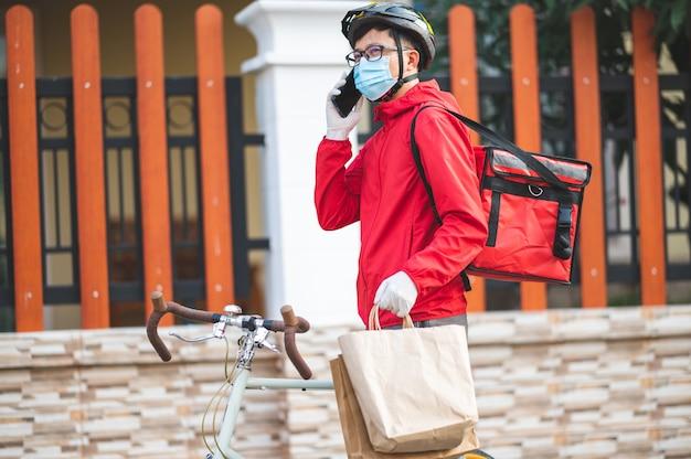 Lieferbote trägt eine gesichtsschutzmaske, um eine rote uniform mit koronavirus zu vermeiden. radfahren, um produkte an kunden zu hause zu liefern.