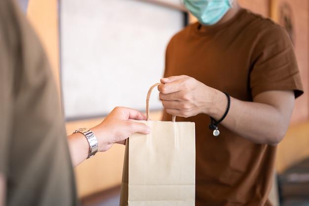 Lieferbote tragen gesichtsmaske und handschuhe, die lebensmittelbeutel für sicherheitsdienst halten