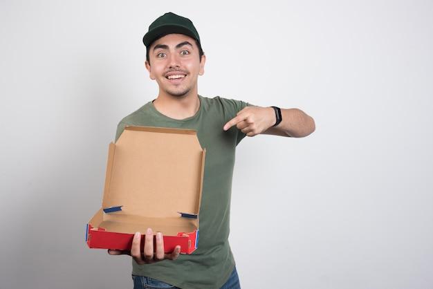 Lieferbote zeigt auf leere pizzaschachtel auf weißem hintergrund.