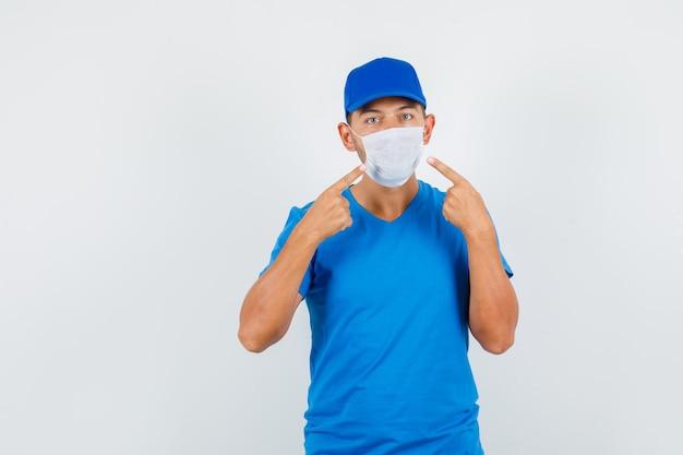 Lieferbote zeigt auf seine maske im blauen t-shirt