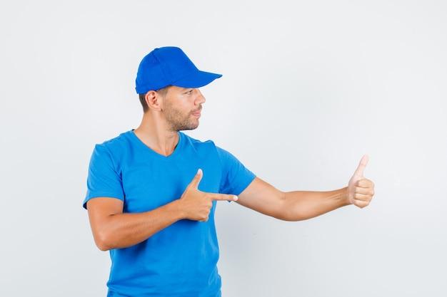 Lieferbote zeigt auf seinen daumen oben im blauen t-shirt
