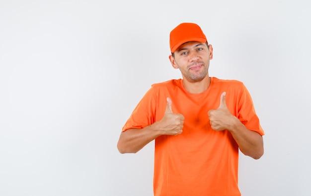 Lieferbote zeigt daumen hoch in orange t-shirt und mütze und sieht fröhlich aus