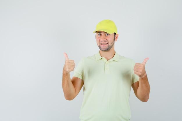 Lieferbote zeigt doppelte daumen in gelber uniform und sieht selbstbewusst aus, vorderansicht.