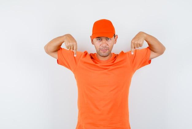 Lieferbote zeigt in orangefarbenem t-shirt und mütze nach unten und sieht sicher aus