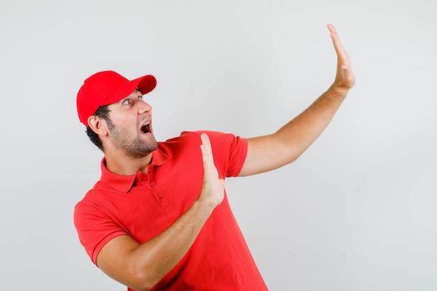 Lieferbote zeigt stoppgeste im roten t-shirt