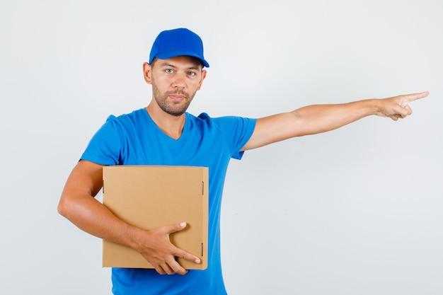 Lieferbote zeigt weg und hält pappkarton im blauen t-shirt