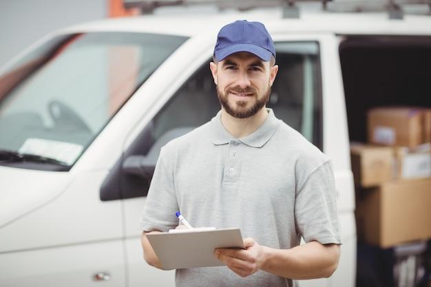 Lieferboteschreiben auf klemmbrett vor seinem packwagen