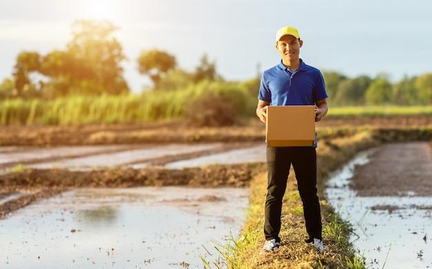 Lieferer, der braune paket- oder pappschachtellieferung zum kunden an der landschaft hält