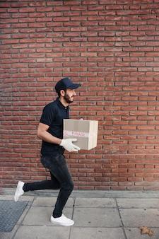 Lieferer, der mit paket vor brickwall läuft