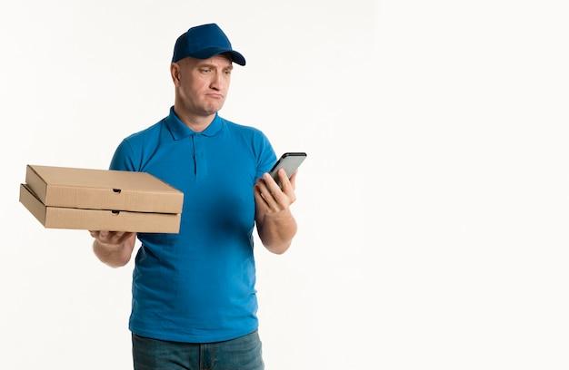 Lieferer, der pizzakästen beim betrachten des telefons hält