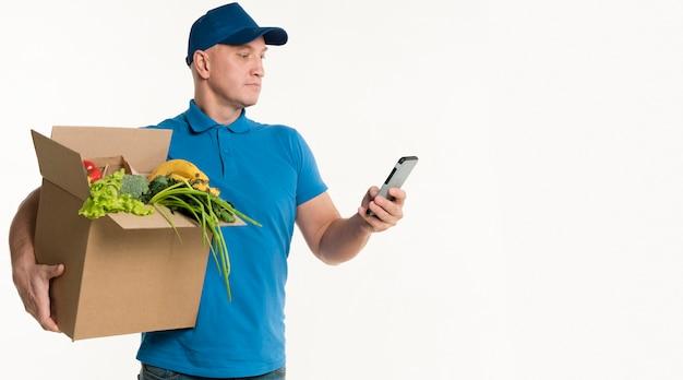 Lieferer, der smartphone beim tragen der einkaufskiste betrachtet