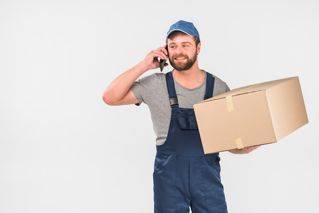 Lieferer mit großem kasten telefonisch sprechend