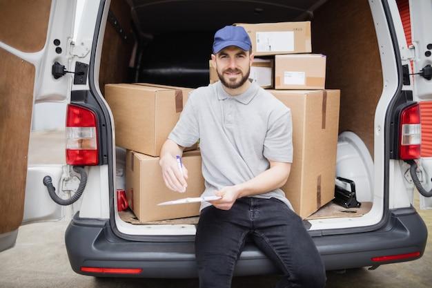 Liefererschreiben auf klemmbrett beim sitzen auf dem laderaum seines packwagens