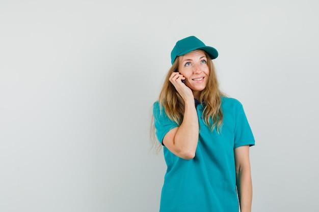 Lieferfrau, die auf handy in t-shirt, mütze und freudig aussehend spricht