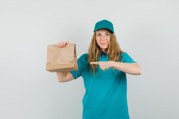 Lieferfrau, die auf papiertüte im t-shirt, in der kappe zeigt und fröhlich schaut.