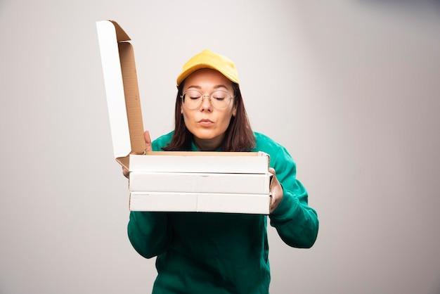 Lieferfrau, die auf pappkartons pizza auf einem weiß schaut. foto in hoher qualität