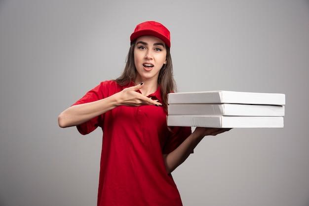 Lieferfrau, die auf pizzen auf grauer wand zeigt.