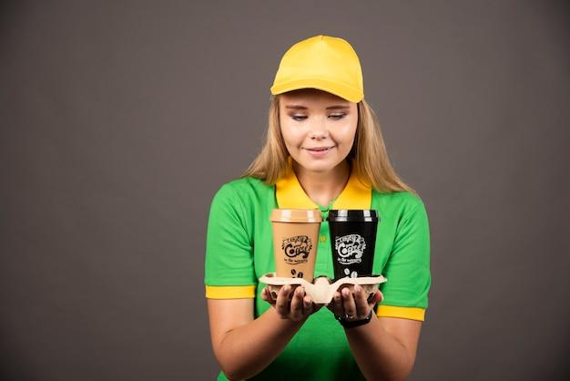 Lieferfrau, die auf tassen kaffee auf schwarzer wand schaut.