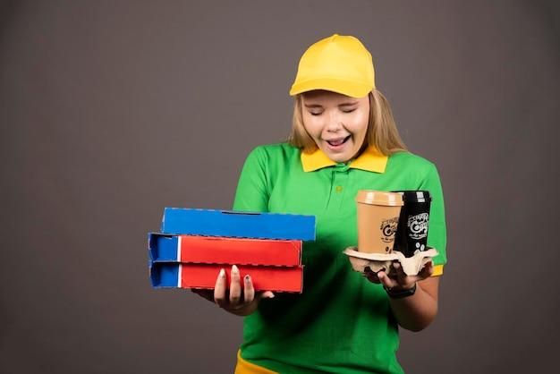 Lieferfrau, die auf tassen kaffee schaut und pappkartons der pizza hält. hochwertiges foto