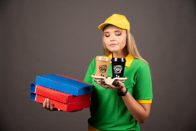 Lieferfrau, die auf tassen kaffee schaut und pappkartons pizza hält.