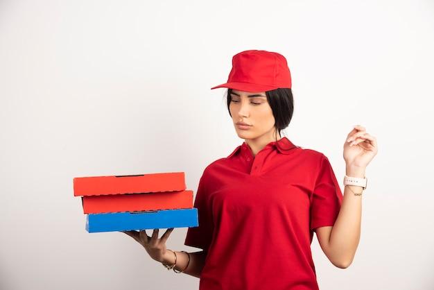Lieferfrau, die bündel von pizzaschachteln auf weißem hintergrund hält.