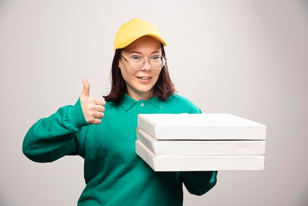 Lieferfrau, die einen daumen zeigt und pappkartons pizza auf einem weiß hält foto in hoher qualität
