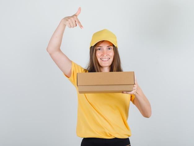 Lieferfrau, die finger auf pappkarton im gelben t-shirt, in der hose, in der kappe zeigt und fröhlich schaut