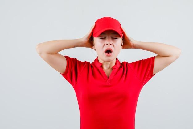 Lieferfrau, die hände zum kopf im roten t-shirt und in der mütze hält und genervt aussieht