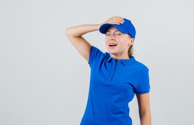 Lieferfrau, die hand auf ihrer kappe im blauen t-shirt hält und hoffnungsvoll aussieht
