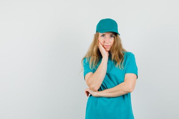 Lieferfrau, die hand auf wange in t-shirt, mütze hält und vernünftig aussieht.