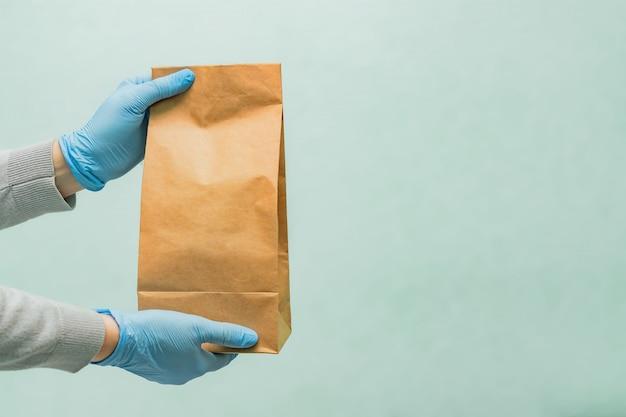Lieferfrau, die handwerkliche papiertüte in medizinischen gummihandschuhen hält. speicherplatz kopieren. schnelle und kostenlose lieferung. online einkaufen. quarantäne