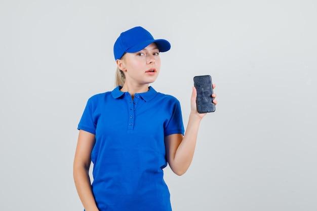 Lieferfrau, die handy im blauen t-shirt und in der kappe hält