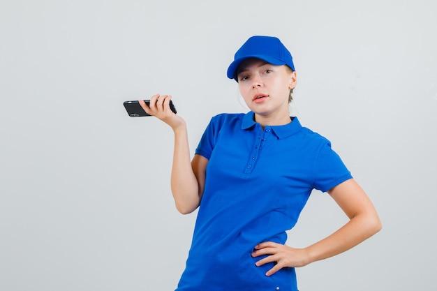 Lieferfrau, die handy mit hand auf taille im blauen t-shirt und in der kappe hält