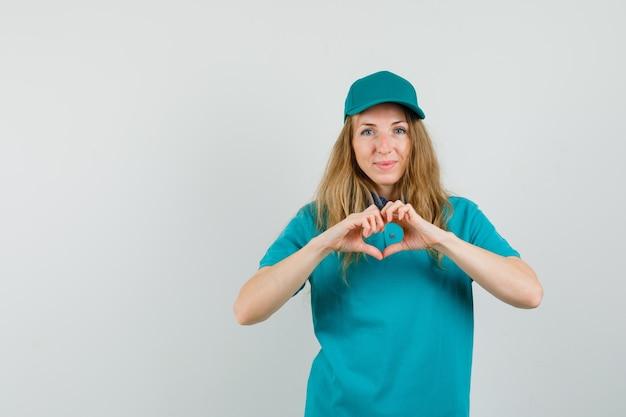 Lieferfrau, die herzgeste in t-shirt, mütze zeigt und fröhlich schaut.