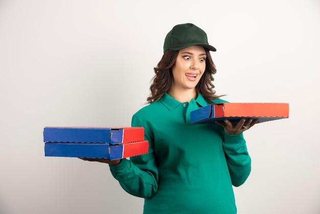 Lieferfrau, die hungrig pizza betrachtet.