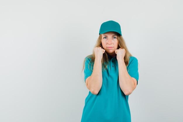 Lieferfrau, die im kampf steht, posiert im t-shirt, in der mütze und sieht mächtig aus.
