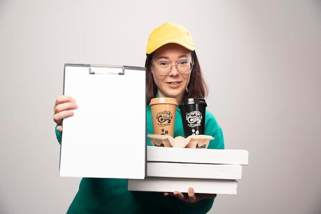 Lieferfrau, die kaffeetassen und notizbuch auf einem weiß hält. foto in hoher qualität