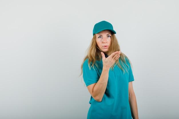 Lieferfrau, die kamera mit erhabener hand im t-shirt, in der kappe betrachtet und vernünftig schaut