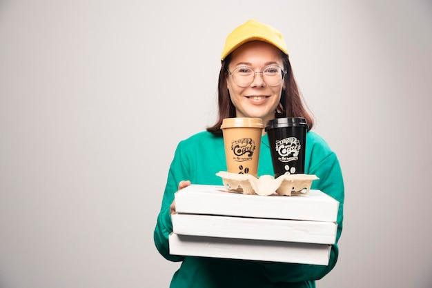 Lieferfrau, die karton kaffeetassen auf einem weiß anbietet. foto in hoher qualität