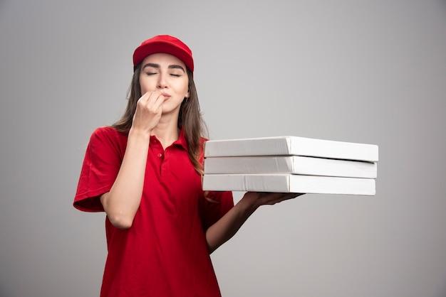 Lieferfrau, die köstliches zeichen über pizzen macht.