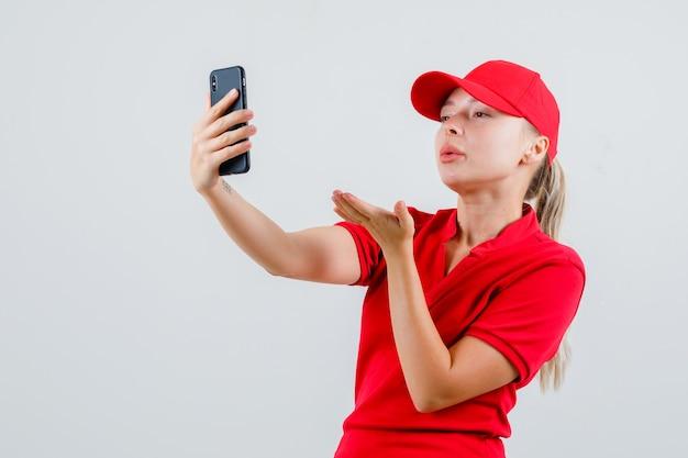 Lieferfrau, die luftkuss auf videoanruf im roten t-shirt und in der kappe sendet