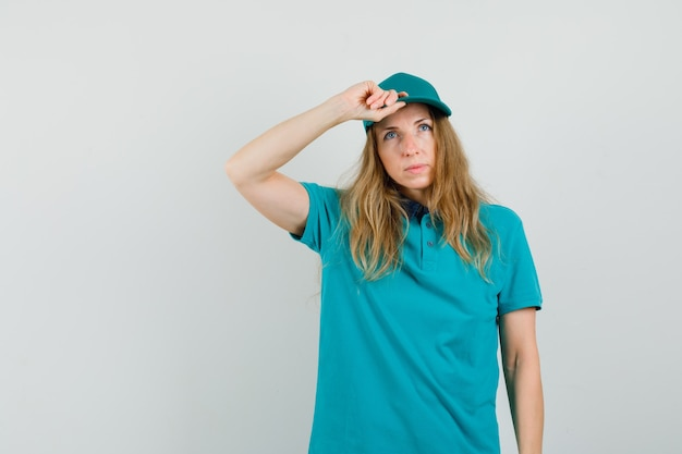 Lieferfrau, die mit hand auf ihrer mütze im t-shirt aufschaut und nachdenklich schaut.