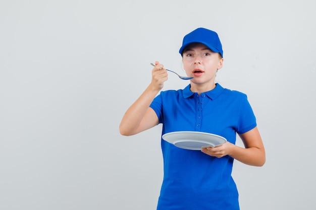 Lieferfrau, die mit löffel im blauen t-shirt und in der kappe isst
