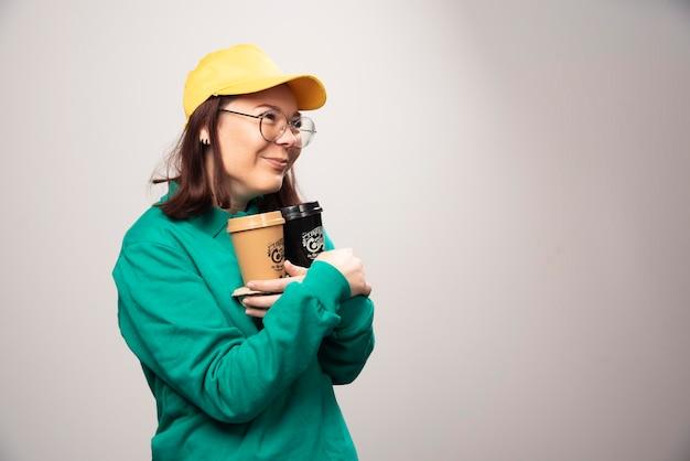 Lieferfrau, die pappe von kaffeetassen auf einem weiß hält. foto in hoher qualität