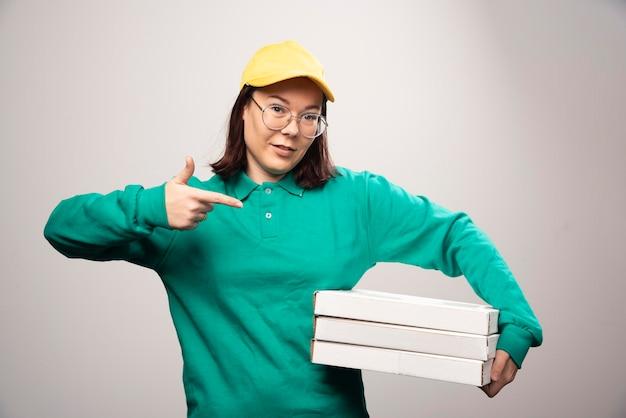 Lieferfrau, die pappkartons der pizza auf einem weiß zeigt. foto in hoher qualität